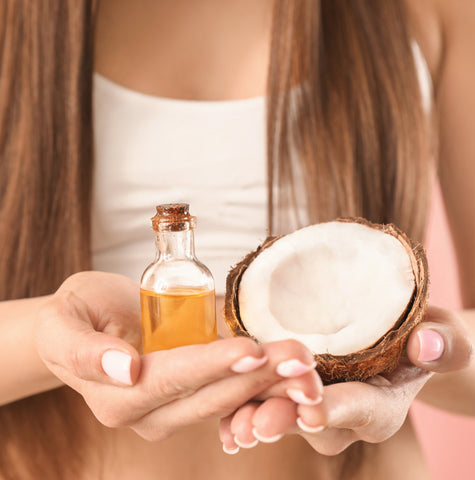 coconut oil in womans hands with coconut pure for repairing hair damage