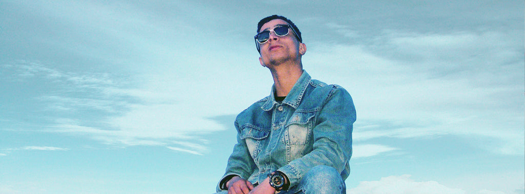Man wearing sunglasses and denim jacket looking up at the sky.