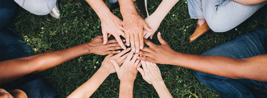 A group of hands together in the middle.