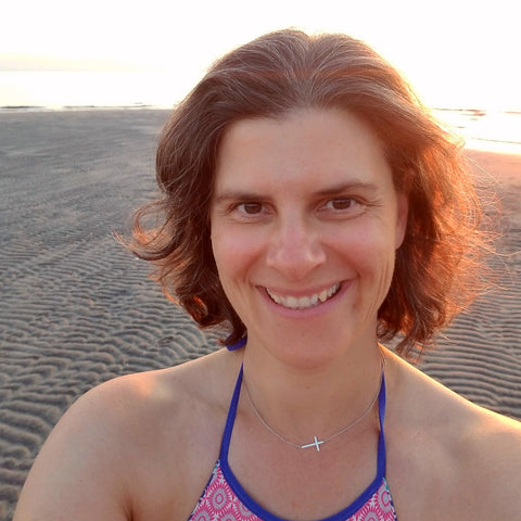 smiling woman at sunrise at beach