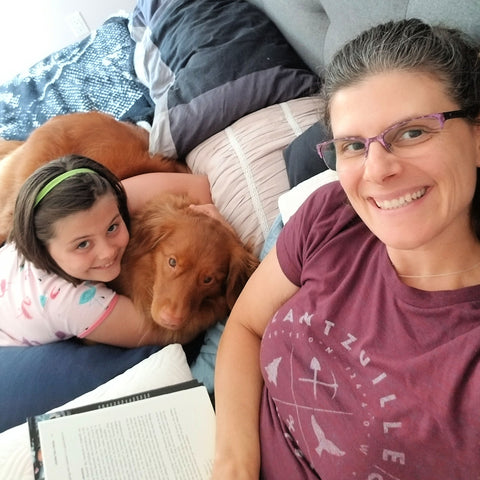 woman reading with her daughter and dog