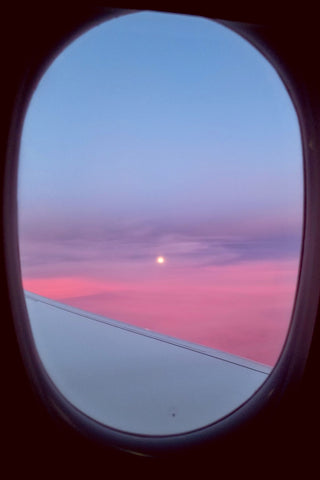 moon rise over pink clouds from the plane