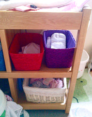 Change table with baskets of nappy inserts and outers