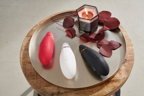 Womanizer Premium in Red, White, Black on Table
