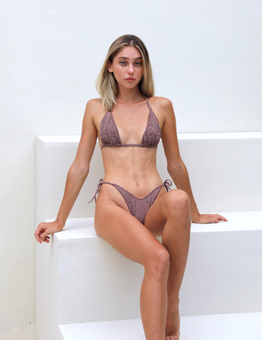 Girl sitting back in sustainable luxury swimwear Thaikila's Vegankini Gaea Opal colored with vegan dye from Eden collection