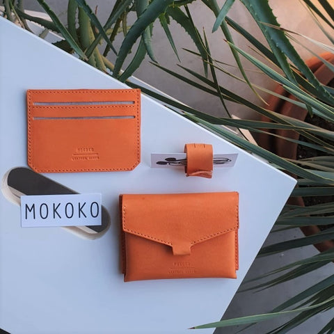 Orange vegetable tanned leather Slim card case, Fold Wallet and cable organizer made in our studio in Tallinn. Photo by Anna Romanova.