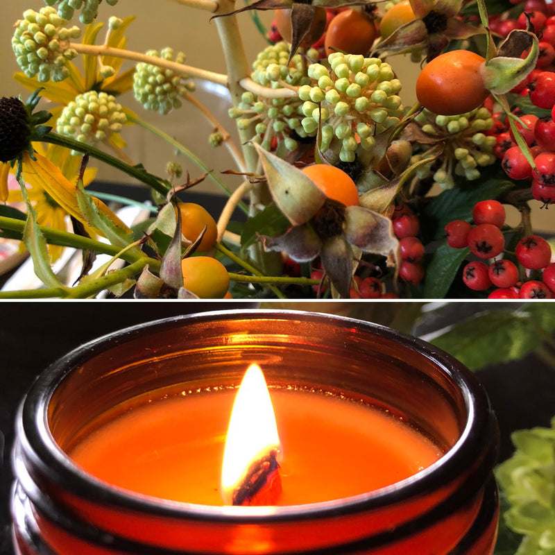 A collection of autumn berries and a lit candle in a jar.
