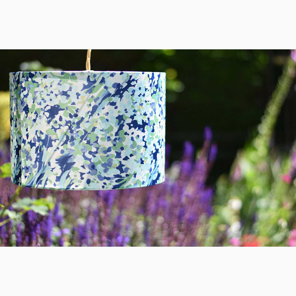 Drum Lamp Shade in Navy, Green and Teal Swirls and Dots in a Garden Setting