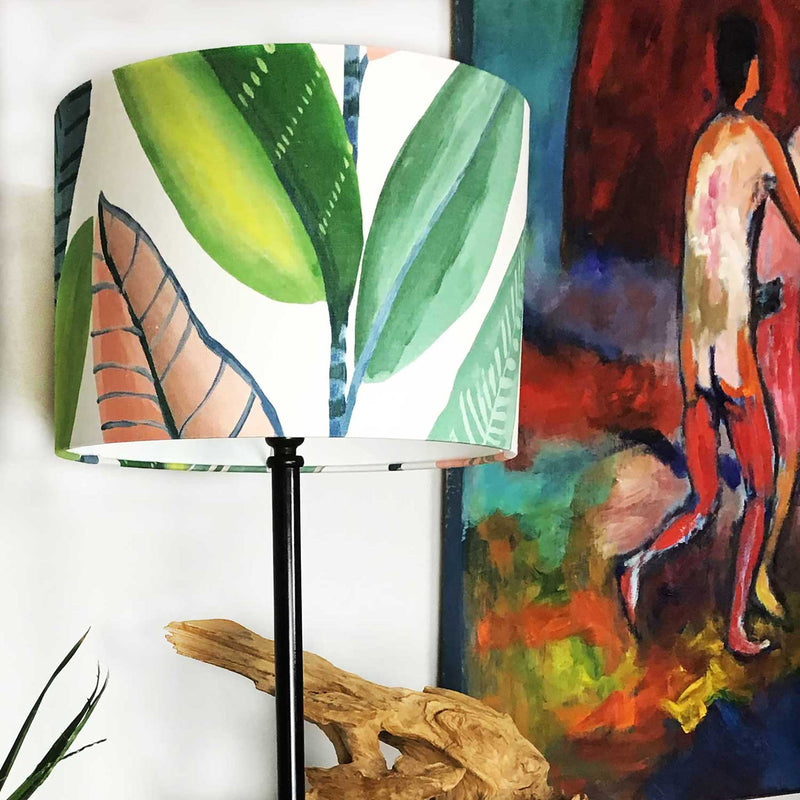 Lamp Shade in Bold Banana Leaves in Pink and Green. Shade is Fitted to a Tall and Think Lamp Base and Sitting on a Sideboard - ZziniHome