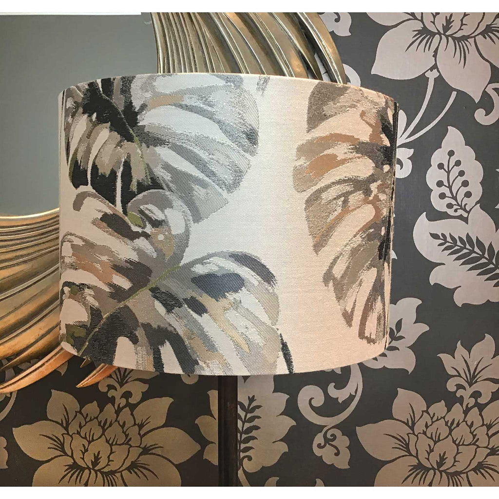 Lamp Shade in Large Cheese Plant Leaves in Greys and Pink Placed in Front of a Golden Mirror and Gilded Wallpaper - ZziniHome