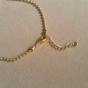 Gold tone ball chain and charm necklace