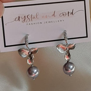 Swarovski crystal pearl and small shiny silver-tone orchid shaped flower drop earrings