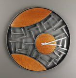 Wall clock with round black metal frame, inside cat eye segments are orange wood surrounded by cut steel nails