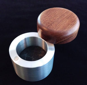 cylindrical engagement ring box, with silver metal base and reddish brown wooden lid, black felt inside