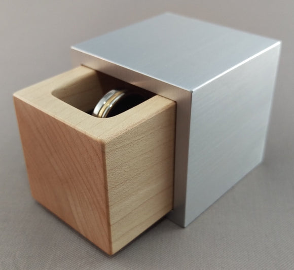 Silver aluminum cube ring box, with blonde maple wooden insert, slightly open to show silver wedding ring
