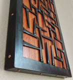 Wood and Metal wall art, black steel frame with pattern of nails across orange red wood surface, copper details along edge of steel frame