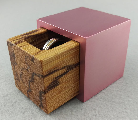 Pink metal engagement ring box, slightly open showing tan marble wood insert with black streaks