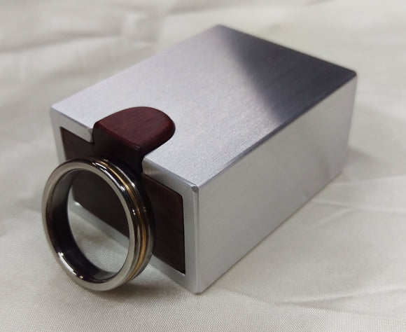 Silver metal engagement ring box with dark wood inside, men's wedding ring propped up to show scale