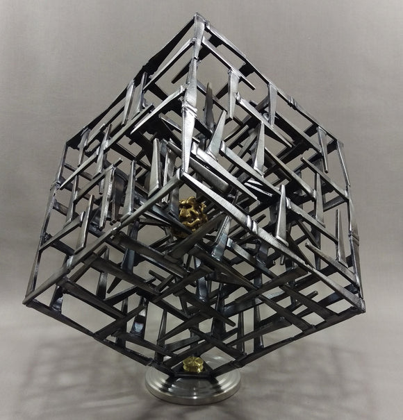 Cube Sculpture made of welded angled black nails, brass brain trapped inside a mesh of nails