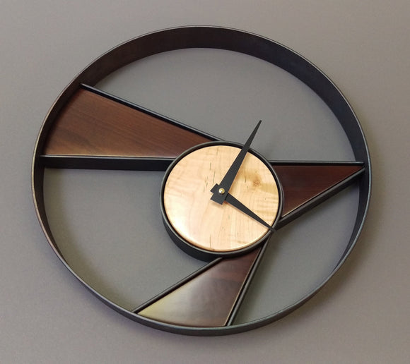 Abstract round steel wall clock, with triangular pieces of dark and light maple inlaid, black clock hands