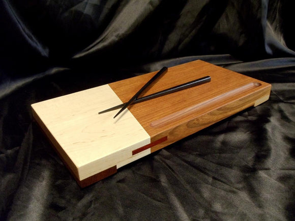 Wooden sushi board, one half light maple, one half darker brown jatoba. black chopsticks