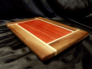 rectangular wooden cutting board. center is red padauk, framed with pinwheel rays of white maple and brown walnut