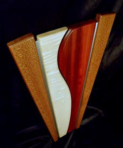 Tapered Wooden wall sculpture, brown lacewood on the outside, surrounding a centerpiece of white figured maple and red Paduak, brushed aluminum inlays