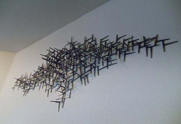 Wide black metal wall sculpture, made from welded nails, overall scion shape