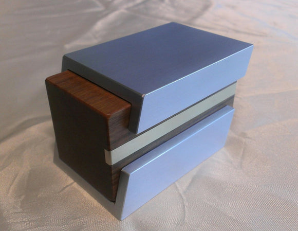 Silver metal engagement ring box with brown wood sliding insert. Metal shell has a cutaway to expose brass line inlay in wood