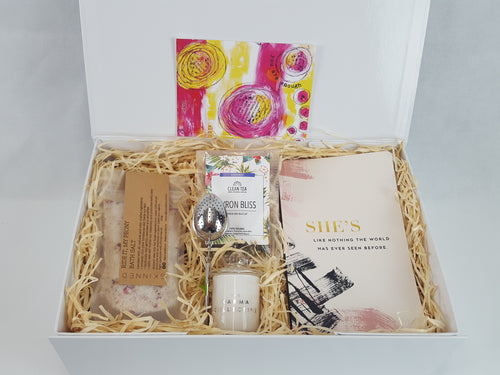White gift box with bath salt, tea,  tea infuser, scented candle and journal