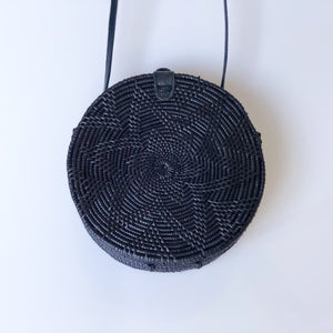 Round rattan ata crossbody handbag in black colour with black leather snap closure and long black leather body strap