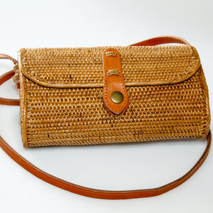 Log shaped rattan ata crossbody handbag in natural colour with tan leather snap closure over envelope-style opening and long tan leather body strap