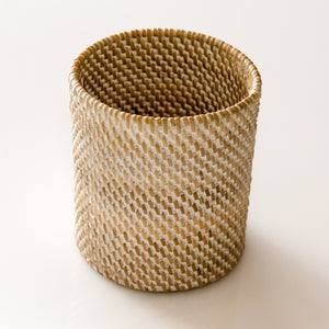 Small woven rattan container formed in a canister shape with whitewash finish