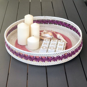 Large woven white rattan tray featuring circular woven pattern on base of tray and braided motif pattern around the raised side, available in either purple or blue colour ways