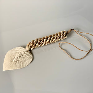 Handmade long tassel made from twine strung with a selection of small natural shells and a cotton macrame tassel shaped into a flat leaf.