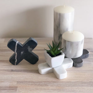 Little black, white and grey decorative crosses carved from marble-look stone, each with their own combination of colour and natural veining.