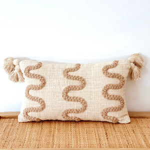 Boho coastal stitched cushion featuring three squiggled lines of tan braid stitched onto a natural eco friendly cotton with two chunky tassels added onto each top corner.