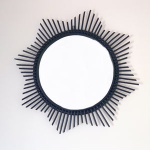 Large round circular rattan mirror featuring spikes cut in the shape of the sun radiating out from the circumference of the 40cm mirror and is available in either a black, natural or white finish