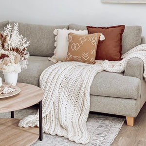 Hamptons-inspired, comfy, coastal, luxurious, super chunky hand-knit throw that is soft and cuddly. Made from an acrylic/wool blend in a natural/white colour.