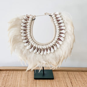 Shell and feather hanging necklace decor on stand.