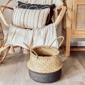 Folding seagrass basket handmade in a loom weave and painted in black on the bottom half and features 2 handles at the top.