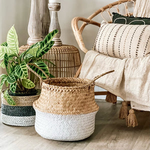 Folding seagrass basket handmade in a loom weave and painted in white on the bottom half and features 2 handles at the top.