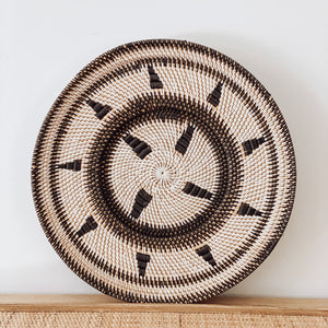 Round handwoven patterned rattan tribal plate wall art in brown and beige colours.