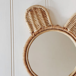 Close up of natural coloured round rattan and wicker mirror in a cute bear ears design.