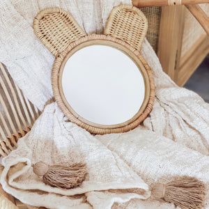 Natural coloured round rattan and wicker mirror in a cute bear ears design, styled on a natural tasselled throw.