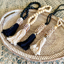 Load image into Gallery viewer, Beaded shell necklace hangings perfect for adding some tribal/coastal luxe to your home décor. Handmade using small wooden beads strung with a selection of small shells and large cotton tassel.
