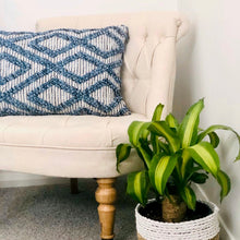 Load image into Gallery viewer, Oblong tactile cushion with blue bauble knot pattern on a natural weave background.
