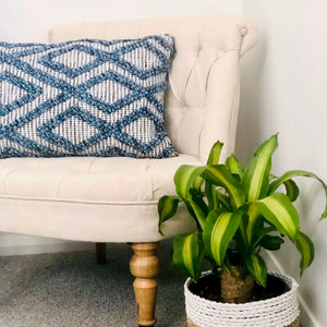 Oblong tactile cushion with blue bauble knot pattern on a natural weave background.