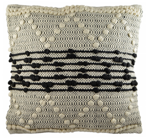 Square cushion featuring black stripes and white zig zag patterns in knotted detail on natural weave background