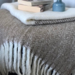 Brushed wool and acrylic throw rug in two-tone camel and white, finished with a chunky white rolled fringe at opposite ends
